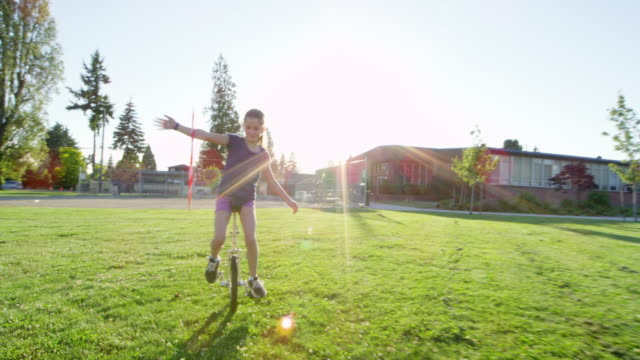 MS TS SLO MO Smiling young girl hula hooping while riding unicycle on field near school