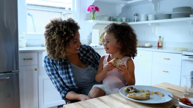 ms smiling young girl sitting in mothers lap eating pizza in kitchen - pizza stock videos & royalty-free footage