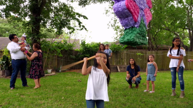 ms pan smiling young girl swinging stick at pinata during family birthday party in backyard - papier stock videos & royalty-free footage