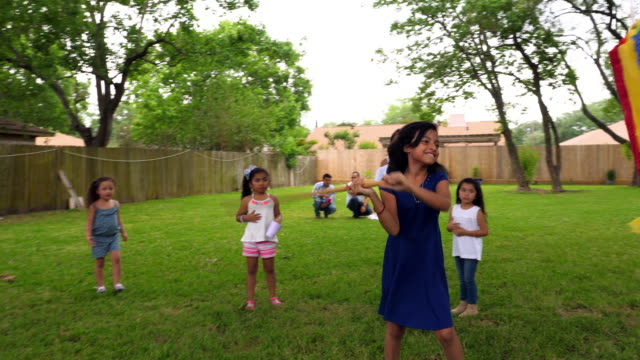 ms smiling young girl trying to break open pinata during family birthday party in backyard - papier stock videos & royalty-free footage