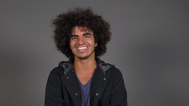 lächelnden schönen jungen mann in schwarzer jacke - gelockt stock-videos und b-roll-filmmaterial