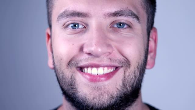 vidéos et rushes de jeune homme beau de sourire regardant l'appareil-photo - regarder fixement