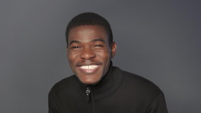 vidéos et rushes de souriant le jeune homme à la recherche de suite en noir à capuche - 25 29 ans