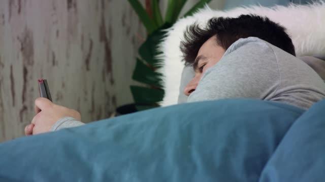 vídeos de stock e filmes b-roll de smiling young man using his smart phone before falling asleep - almofada roupa de cama