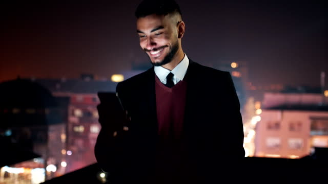 smiling young man using phone on rooftop - males stock videos & royalty-free footage