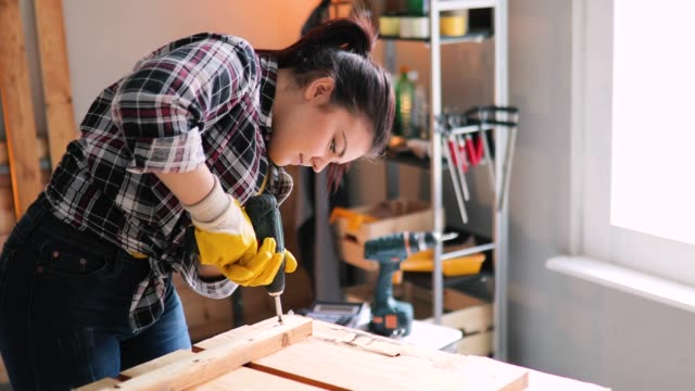 smiling young professional female carpentry worker with electric screwdriver on the table in the workshop - timber stock videos & royalty-free footage