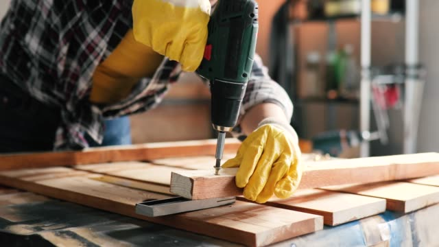 smiling young professional female carpentry worker with electric screwdriver on the table in the workshop - diy stock videos & royalty-free footage