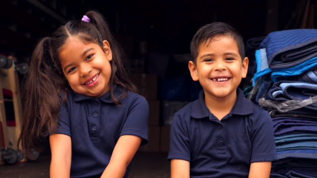 cu smiling young siblings sitting on back of moving truck while family moves - sibling stock videos & royalty-free footage