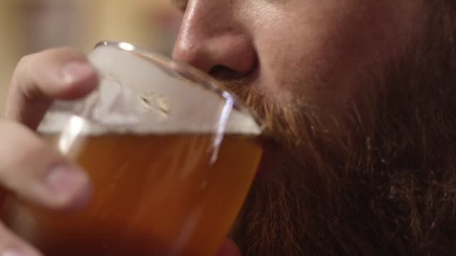 vídeos de stock e filmes b-roll de a smiling young white man with a red beard drinks a beer - copo