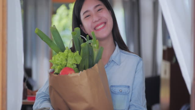 smiling young woman and holding a bag full of healthy food in the kitchen. having fun while making food for healthy,body-positive women - stereotypical homemaker stock videos & royalty-free footage