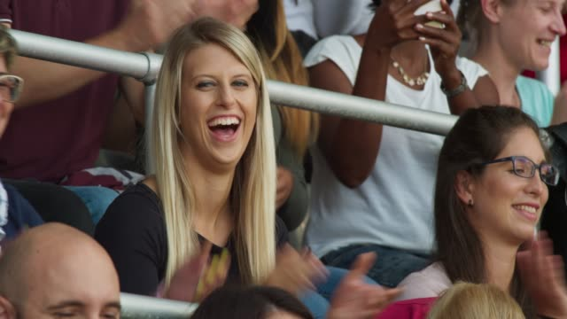 Smiling young woman cheering sitting on the stadium tribune