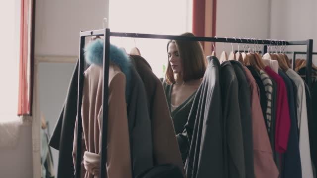 smiling young woman choosing coat - casacca video stock e b–roll