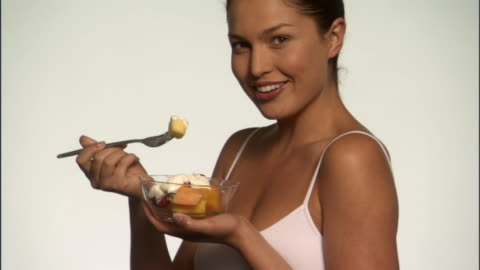 slo mo, cu, smiling young woman eating fruits with yogurt in studio, portrait - enjoyment stock videos & royalty-free footage