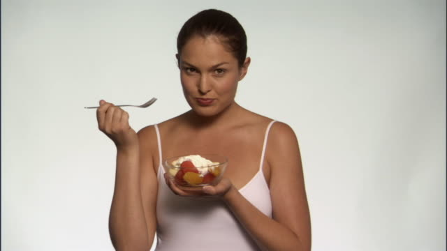 SLO MO, MS, Smiling young woman eating fruits with yogurt in studio, portrait