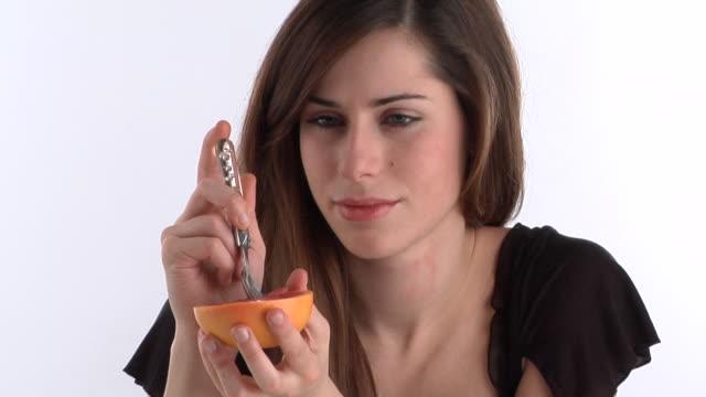 CU, Smiling young woman eating grapefruit, portrait