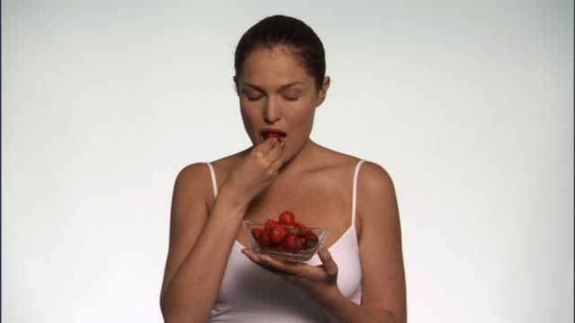 slo mo, ms, smiling young woman eating strawberries in studio, portrait - see other clips from this shoot 125 stock videos and b-roll footage