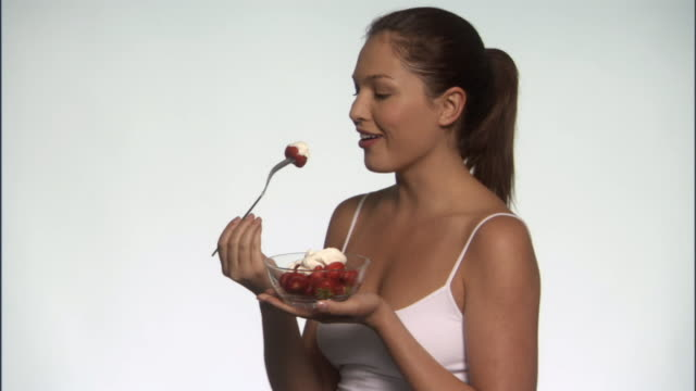 slo mo, ms, smiling young woman eating strawberries with whipped cream in studio, portrait - see other clips from this shoot 125 stock videos and b-roll footage