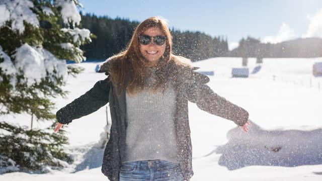 Leende ung kvinna njuter av vintern på en solig dag