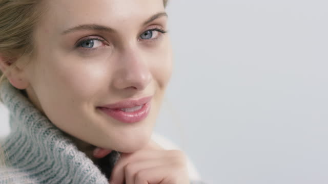 smiling young woman feeling cozy in soft sweater - model stock videos & royalty-free footage