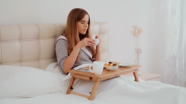 Smiling young woman having breakfast in bed.