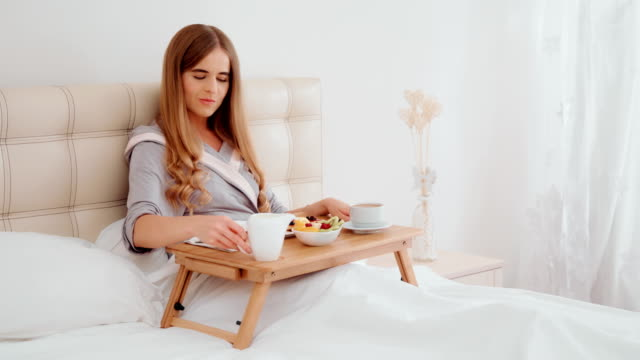 smiling young woman having breakfast in bed. - tray stock videos & royalty-free footage