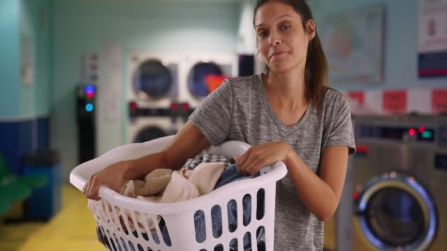 smiling young woman holding basket of clothes in laundry room - tvättmedel bildbanksvideor och videomaterial från bakom kulisserna