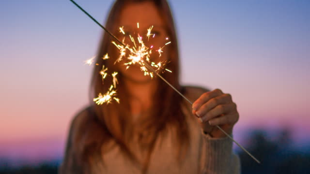 stockvideo's en b-roll-footage met jonge vrouw met brandende sparkler glimlachen - jubileum