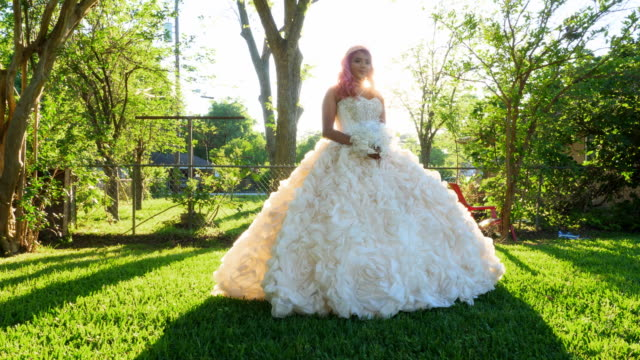ms pan smiling young woman in backyard dressed in quinceanera gown - 14 15 anni video stock e b–roll