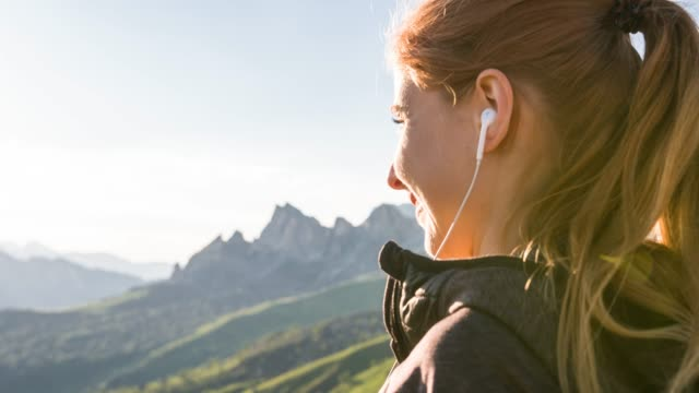 smiling young woman in mountainside inserting earphones, listening to music on smartphone, admiring the view - mp3 player stock videos & royalty-free footage