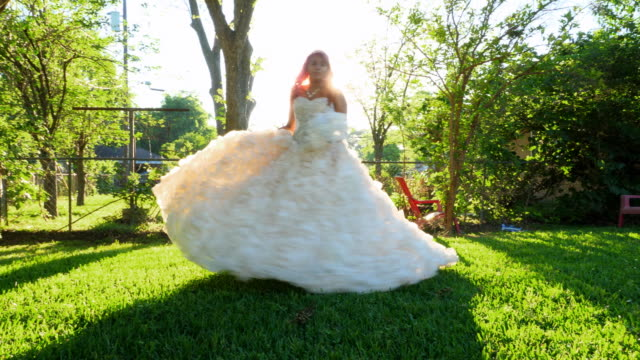 ms smiling young woman in quinceanera gown twirling in backyard before quinceanera - 14 15 anni video stock e b–roll