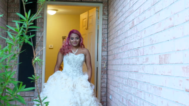 MS Smiling young woman in quinceanera gown walking out front door of home