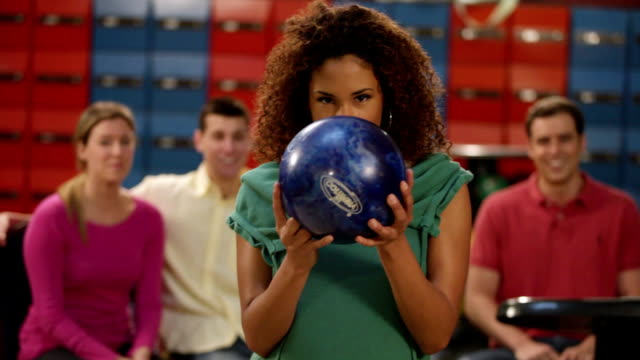 ms smiling young woman lining up to roll bowling ball, friends in background / dover, new hampshire, usa - bowling ball stock videos & royalty-free footage