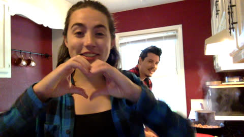 vidéos et rushes de smiling young woman makes a heart shape with her hands while on video call - webcam