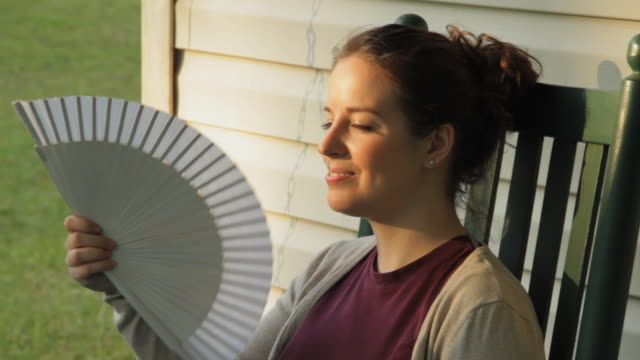 cu smiling young woman on rocking chair with fan / madison, florida, usa - hand fan stock videos & royalty-free footage