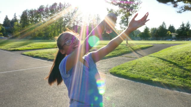 ms smiling young woman shooting jump shot on outdoor court on summer evening - jump shot stock videos and b-roll footage