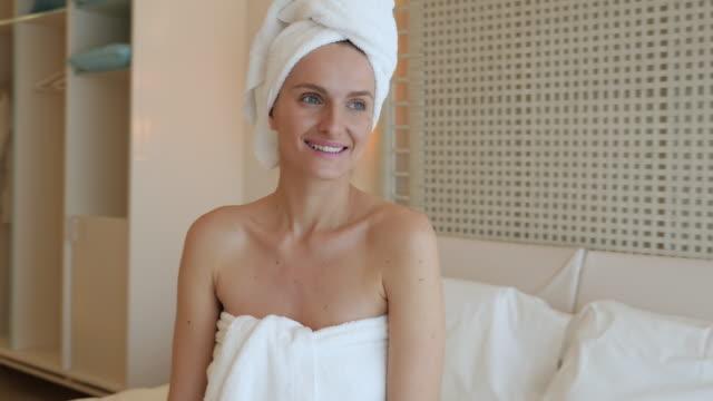 vídeos de stock, filmes e b-roll de sorrindo jovem mulher sentada na cama - toalha