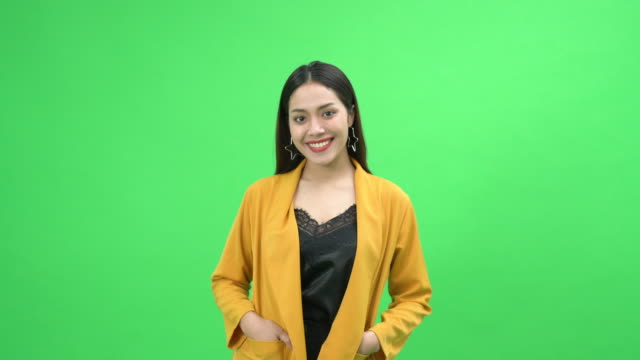 smiling young woman standing in front of green background - standing stock videos & royalty-free footage