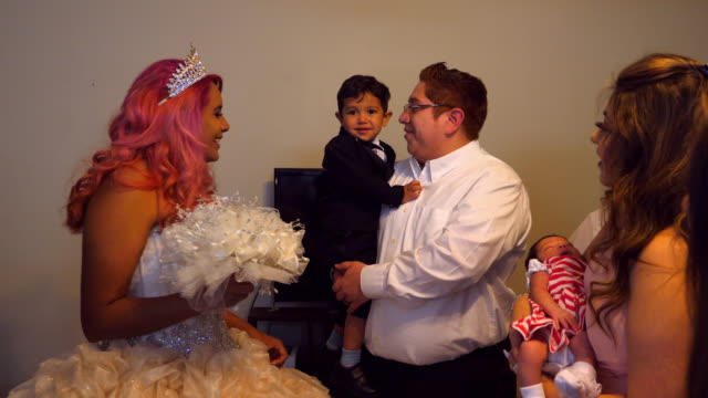 ms smiling young woman standing in living room with family dressed in quinceanera gown - 14 15 anni video stock e b–roll