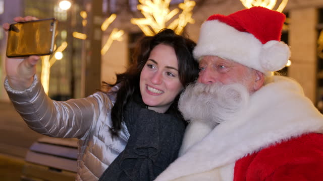 smiling young woman taking selfie with santa claus outdoors - father christmas stock videos & royalty-free footage