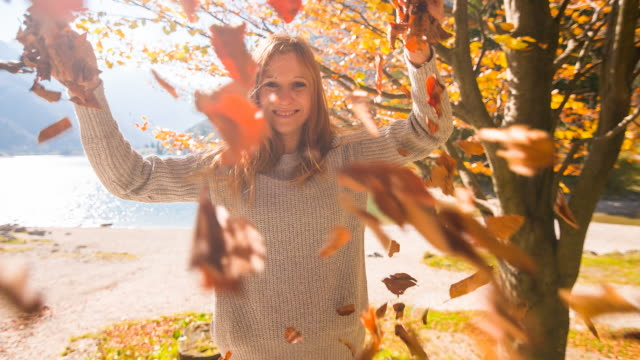 lächelnde junge frau werfen herbst blätter in der luft - naturwald stock-videos und b-roll-filmmaterial