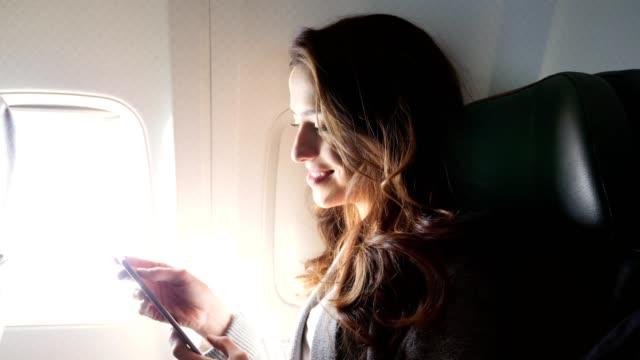 Glimlachende jonge vrouw maakt gebruik van smartphone tijdens de vlucht