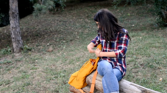 smiling young woman using digital tablet in the park - bag stock videos & royalty-free footage