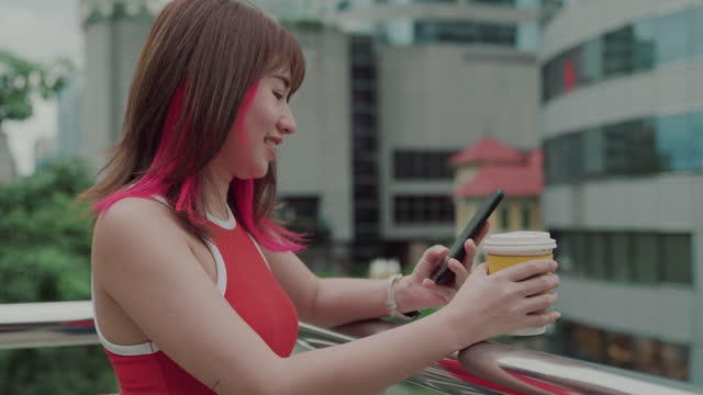 smiling young woman using smartphone and looking view in the city - drinking stock videos & royalty-free footage