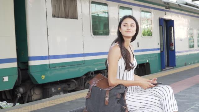 vídeos y material grabado en eventos de stock de jovencita sonriente esperando el tren. - estación de tren