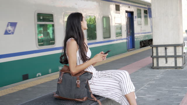 smiling young woman waiting for the train. - stazione della metropolitana video stock e b–roll