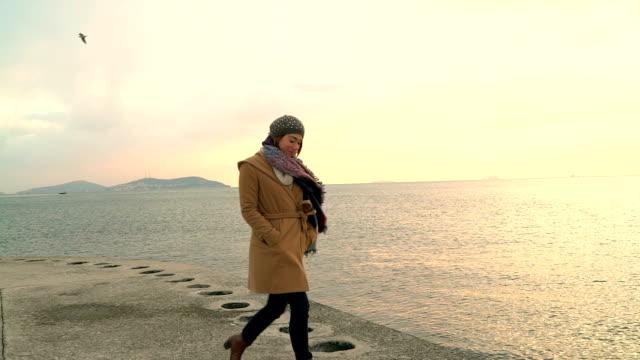 hd : lächelnde junge frau zu fuß am strand - in den zwanzigern stock-videos und b-roll-filmmaterial
