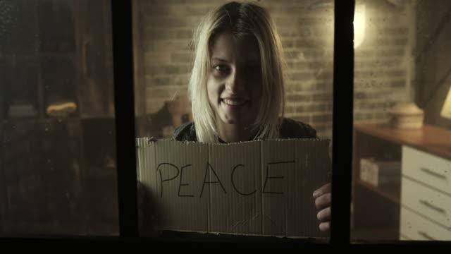 vídeos y material grabado en eventos de stock de sonriente mujer joven sostienen paz tarjeta - símbolo de la paz conceptos