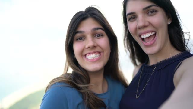 vídeos de stock, filmes e b-roll de mulheres novas de sorriso que tomam um selfie em rio de janeiro - irmã