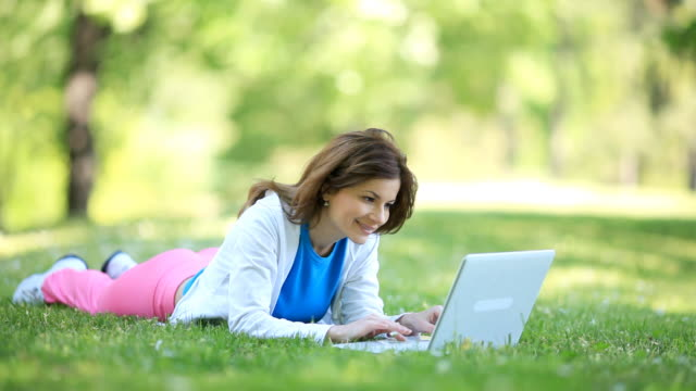 Smilng girl typing on laptop in the park.
