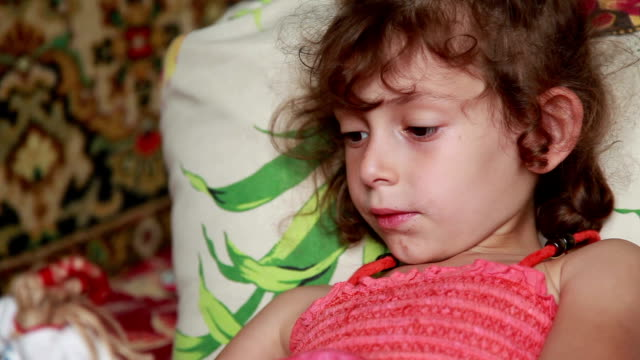 smirking little girl lays on the bed and plays with a doll - smirking stock videos and b-roll footage